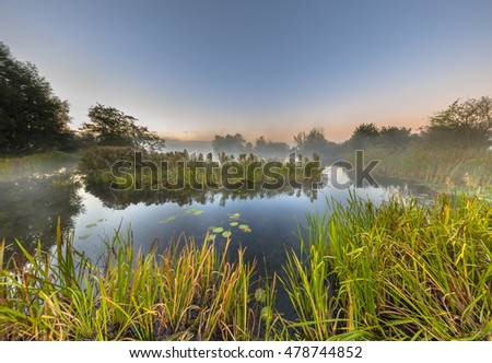 Marshland river system under foggy morning sunrise in september. Province of Drenthe, Netherlands.