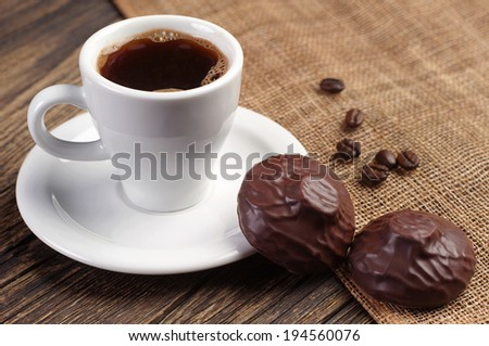 Marshmallow and cup of coffee on wooden table