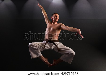 Martial arts fighter during flying moments after jumping. Artistic studio lighting.  - stock photo