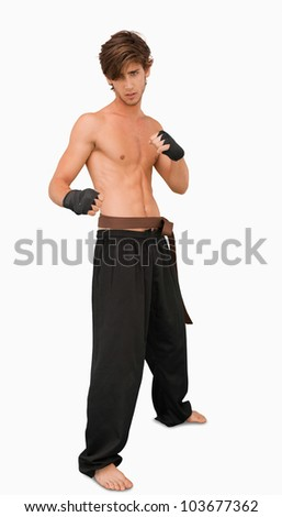 Martial arts fighter standing in fighting pose against a white background - stock photo