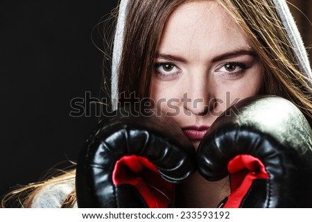 Martial arts or self defense concept. Sport boxer woman in gloves. Fitness girl training kick boxing on black background - stock photo