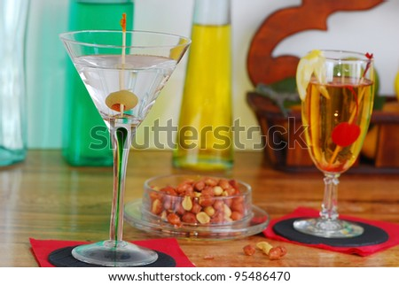 Martini and Whiskey Sour cocktails on wooden bar with spicy peanuts and colorful bottles in background.