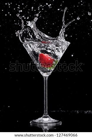 Martini drink splashing out of glass, isolated on black background - stock photo