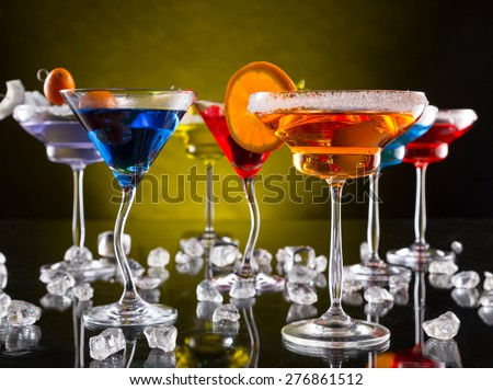 Martini drinks served on glass table with colored dark background - stock photo