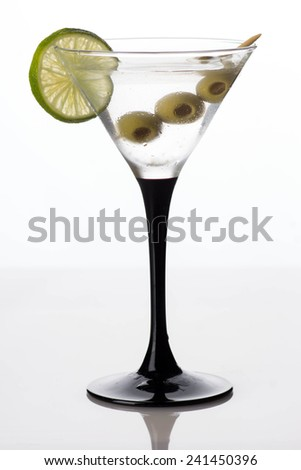 Martini glass and alcohol with green olives isolated on white background - stock photo