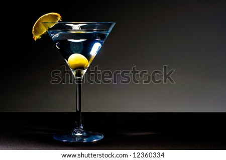 martini glass on black with olive - stock photo