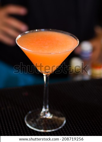 Martini Glass with a passion fruit cocktail at the bar - stock photo