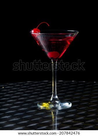 Martini Glass with a red cocktail on a black background - stock photo