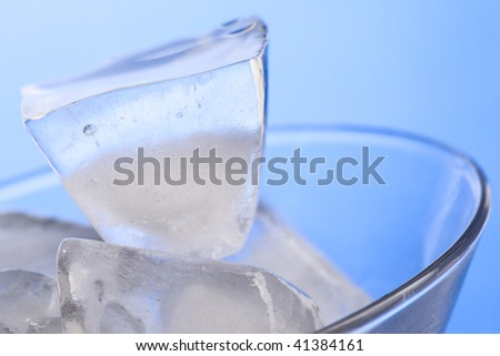Martini glass with ice cubes on blue background, closeup