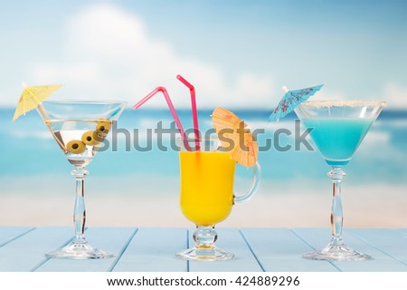Martini glass with olives, drink and juice on the background of the sea. - stock photo