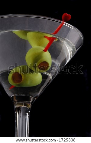 Martini Glass With Stuffed Olives On A Red Cocktail Stick - stock photo