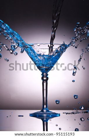 Martini glass with water splash with a blue color tint - stock photo