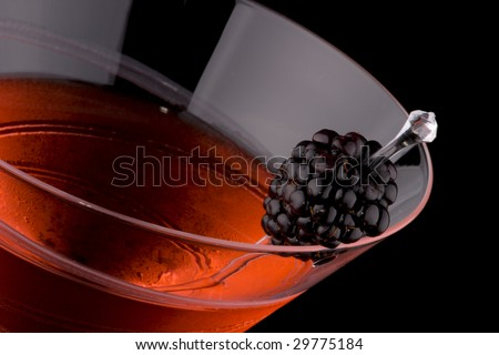 Martini in chilled glass over black background on reflection surface. Red color, made with blackberry liqueur and garnished with fresh blackberry. Most popular cocktails series. - stock photo