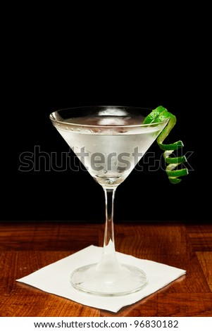 martini on a bar top garnished with a fresh lime twist