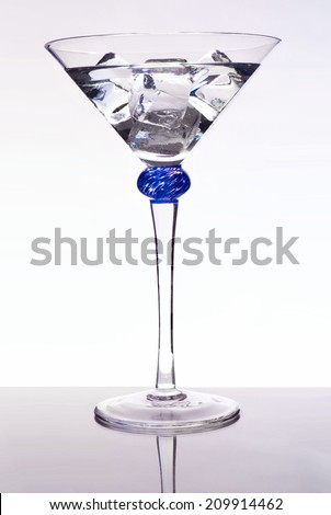 Martini on the rocks. Martinis are one of the most popular cocktails, is typically made with gin and vermouth, but there are also vodka martinis. This example has no garnish. Shot on reflective table - stock photo