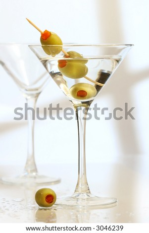 Martini with 3 olives on bar counter - stock photo
