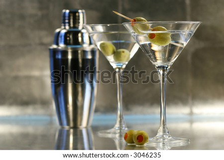 Martinis with olives and shaker on bar - stock photo