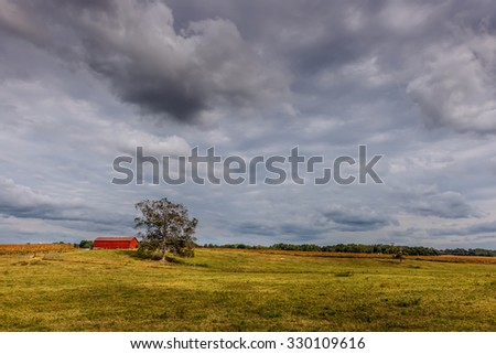 Maryland Farm in early Autumn with red barn and Oak tree - stock photo