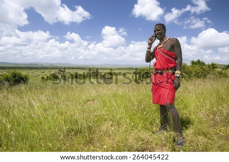 Masai in red toga talks on his cell phone from the grasslands of the Lewa Wildlife Conservancy in North Kenya, Africa - stock photo