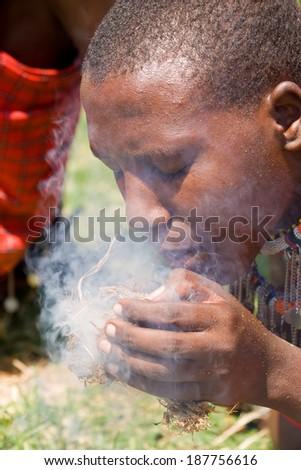 Masai making fire in Masai Mara National park, Kenya - stock photo
