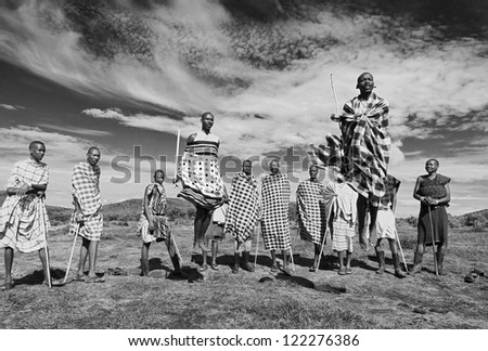 MASAI MARA, KENYA - DECEMBER 2: Unidentified Masai warriors dance and participate in traditional jumps as part of a cultural ceremony on December 2, 2011 in Masai Mara National Park, Masai Mara, Kenya - stock photo