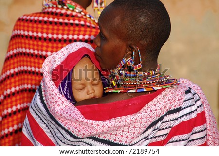 MASAI MARA, KENYA - JULY 13: Masai mother with her child on circa July 13, 2009 in Masai, Kenya. The woman wears traditional jewelry forgings of small colored beads. - stock photo