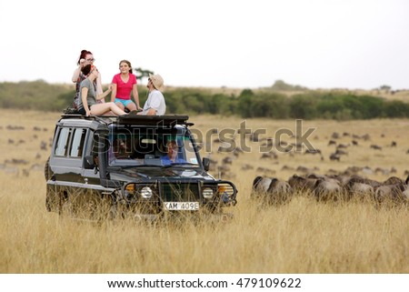 MASAI MARA, KEYNA-AUGUST 19: Tourist enjoying game drive on safari Jeep with open roof in Masai Mara National Reserve on August 19, 2016 at Masai Mara, Kenya, Africa