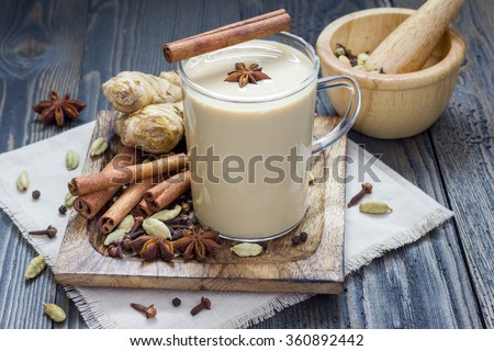 Masala chai with spices. Cinnamon stick, cardamom, ginger, clove, star anise, black pepper. - stock photo
