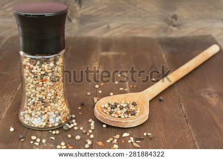 Masala indian spice mix on wooden background. Glass grinder and wooden spoon with spices - stock photo
