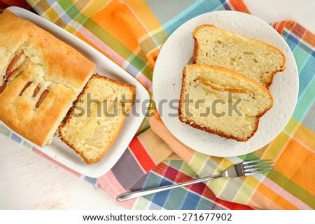 Mascarpone cake slice, long fork on white bright background top view - stock photo