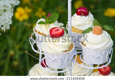 Mascarpone cupcakes with berries on top, on a stand - stock photo