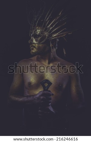 masculine, golden bodypaint, man with gold helmet, ancient warrior deity - stock photo