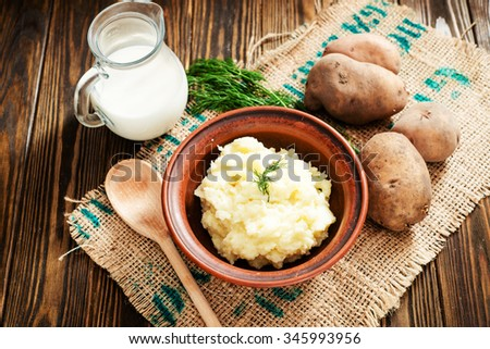 mashed boiled potato with herbs. milk and spices on a wooden background - stock photo