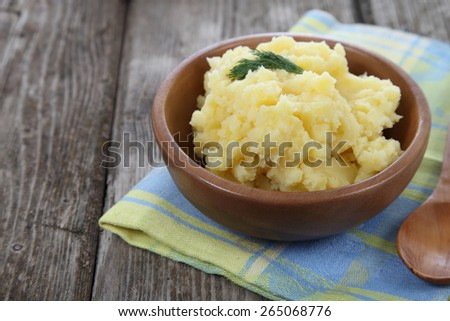 Mashed potatoes in a wooden plate on the table - stock photo