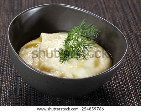 mashed potatoes wiyh fennel in black bowl on dark background - stock photo