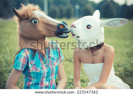 mask horse and rabbit women sisters friends using smartphone and tablet in the park - stock photo