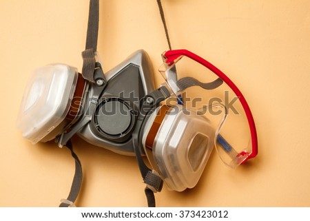 Mask respirator and goggles on the wall. Copy space - stock photo