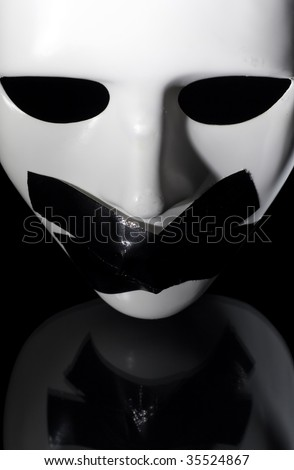mask shot from above with masking tape on it's mouth ,on reflective surface,clipping path available - stock photo