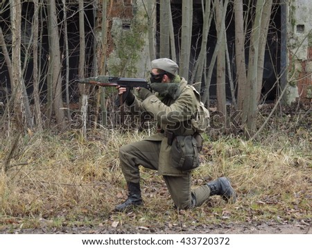 Masked airsoft player, who plays for Russian side of the army, old time scenery - stock photo