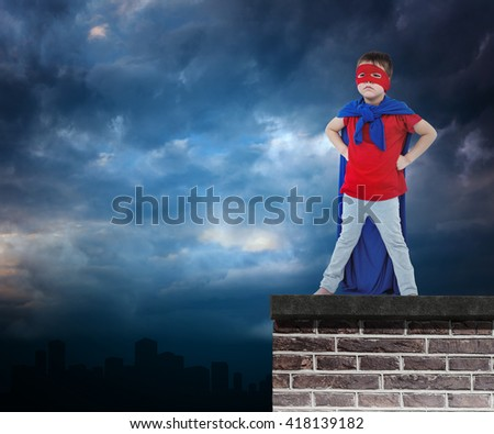Masked boy pretending to be superhero against red brick wall - stock photo