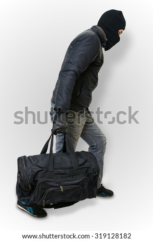 Masked burglar or thief with balaclava is sneaking with black bag on white background. - stock photo