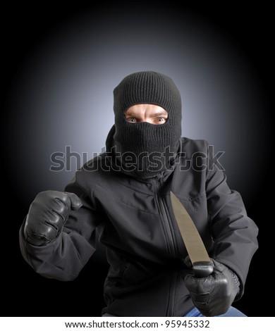 Masked criminal holding a knife - stock photo