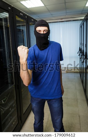 Masked cyber hacker wearing a balaclava threatens with fist in data center on the background.