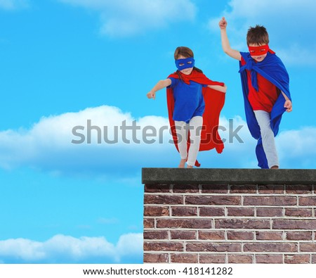 Masked kids walking pretending to be superheroes against red brick wall - stock photo