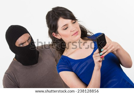 masked male thief robbing beautiful young happy girl talking on cell phone from behind - stock photo