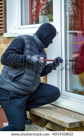 Masked man breaking-in house - stock photo
