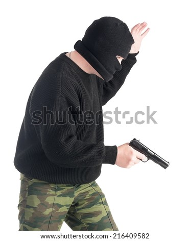 """Masked man with gun makes """"come with me"""" sign over white background - stock photo"""
