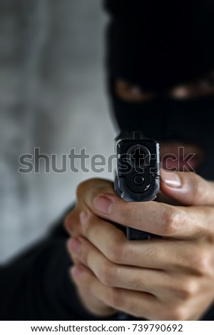 Masked robber with gun aiming into the camera against a black background.Selective focus.