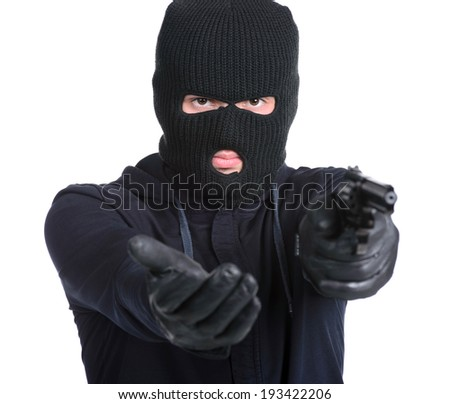 Masked robber with gun aiming into the camera against a white background