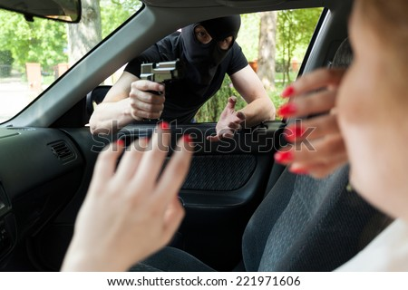 Masked robber with gun threatens a woman in car - stock photo